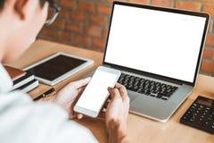 Homem de negócio que usa o portátil e o telefone celular com a tela vazia no escritório fotografia de stock royalty free