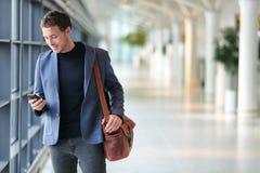 Homem de negócio que usa o telefone celular app no aeroporto