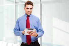 Homem de negócio que usa sua tabuleta Fotos de Stock Royalty Free