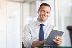 Homem de negócio que usa a tabuleta digital fotografia de stock