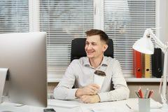 Homem de negócio sério e redigido na camisa que senta-se na mesa, trabalhando no computador com monitor moderno Gerente ou trabal imagens de stock