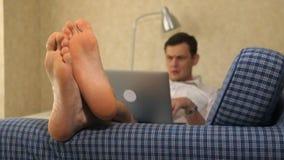Homem de negócio sério que encontra-se no sofá, trabalhando com o portátil, pensativo pés, close-up filme