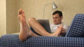 Homem de negócio sério que encontra-se no sofá, trabalhando com o portátil, riscando os pés pés, close-up video estoque