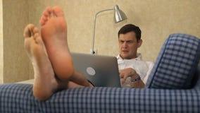 Homem de negócio sério que encontra-se no sofá, trabalhando com portátil, paixão pés, close-up video estoque