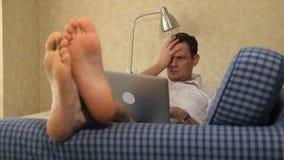 Homem de negócio sério que encontra-se no sofá, trabalhando com portátil, paixão pés, close-up filme