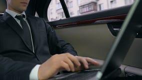 Homem de negócio seguro que senta-se no banco traseiro do carro e que usa o portátil, projeto de trabalho filme