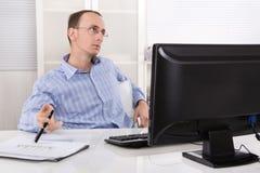 Homem de negócio triste e sobrecarregado desatento que senta-se na mesa com co Fotografia de Stock Royalty Free