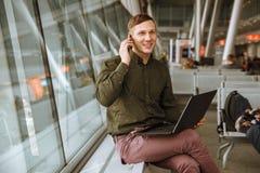 Homem de negócio urbano que fala no telefone esperto para dentro no aeroporto fotografia de stock