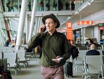 Homem de negócio urbano que fala no telefone esperto para dentro no aeroporto imagens de stock royalty free