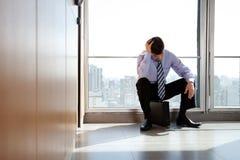 Homem de negócio virado que senta-se na pasta Fotos de Stock