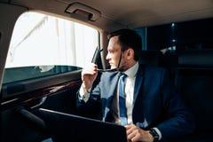 Homem de negócios à moda novo nos óculos de sol no assento traseiro do carro imagem de stock