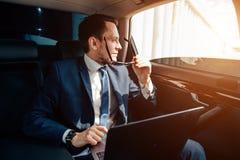 Homem de negócios à moda novo nos óculos de sol no assento traseiro do carro fotografia de stock royalty free