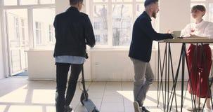 Homem de negócios à moda novo que monta o 'trotinette' elétrico no escritório na moda moderno, falando aos colegas Local de traba filme
