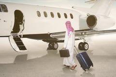Homem de negócios árabe que anda para o jato fotos de stock royalty free