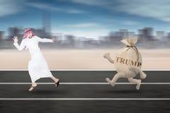Homem de negócios árabe que corre com palavra do trunfo Imagens de Stock Royalty Free