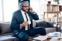 Homem de negócios árabe que fala no telefone no sofá na sala do escritório foto de stock