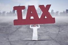 Homem de negócios árabe que levanta uma palavra grande e pesada do imposto com os arranha-céus no fundo Imagem de Stock