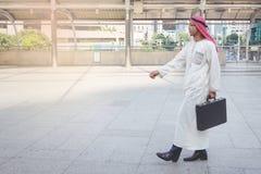 Homem de negócios árabe que mantém o saco sentimento bem sucedido, bom foto de stock