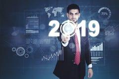 Homem de negócios árabe que pressiona os números 2019 fotos de stock