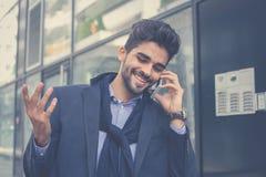 Homem de negócios árabe que usa o telefone esperto exterior imagens de stock