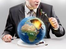 Homem de negócios ávido que come a terra do planeta fotos de stock royalty free