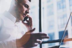 Homem de negócios adulto farpado da foto que trabalha no escritório moderno do sótão Camisa branca vestindo do homem e smartphone fotos de stock royalty free