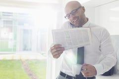 Homem de negócios adulto meados de na chamada ao guardar o copo do jornal e de café em casa foto de stock royalty free