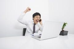 Homem de negócios adulto meados de que cheering no telefone celular na mesa no escritório imagens de stock royalty free