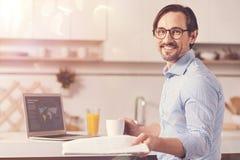 Homem de negócios adulto positivo que senta-se na cozinha fotografia de stock royalty free