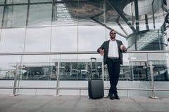 Homem de negócios adulto que está ao lado do aeroporto que guarda a xícara de café imagens de stock royalty free