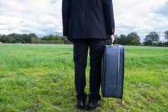 Homem de negócios adulto que guarda uma mala de viagem fotografia de stock