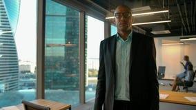 Homem de negócios de Aframerican que põe sobre vidros e que olha a câmera filme