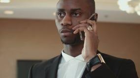 Homem de negócios africano, americano que fala no telefone