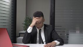 Homem de negócios africano bem sucedido novo em um terno que mostra a emoção da decepção, facepalm, sentando-se no escritório 60 filme
