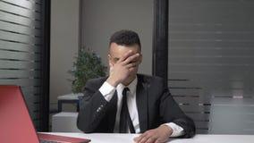 Homem de negócios africano bem sucedido novo em um terno que mostra a emoção da decepção, facepalm, sentando-se no escritório 60 vídeos de arquivo