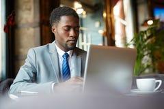 Homem de negócios africano considerável Using Laptop fotografia de stock