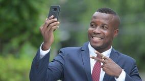 Homem de negócios africano feliz novo que toma o selfie fora video estoque