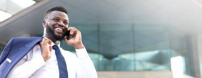 Homem de negócios africano feliz que guarda seu telefone ao estar perto da construção e ao olhar a direito imagem de stock
