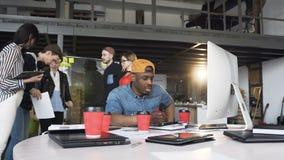 Homem de neg?cios africano focalizado que trabalha no computador quando seu cowoker que discute dados do diagrama no vidro video estoque