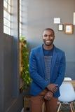 Homem de negócios africano novo que está apenas em um sorriso moderno do offce imagem de stock royalty free