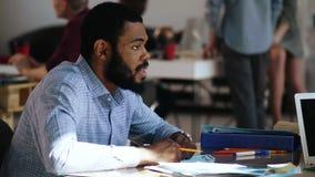 Homem de negócios africano novo sério profissional do close-up que fala, escutando o colega na tabela na moda do escritório do só filme