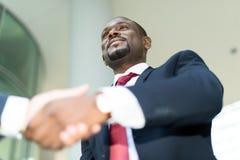 Homem de negócios africano que agita as mãos com caucasiano Fotografia de Stock