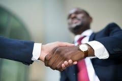 Homem de negócios africano que agita as mãos com caucasiano Imagens de Stock