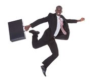 Homem de negócios africano que corre guardando a pasta Fotos de Stock