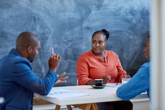 Homem de negócios africano que fala aos colegas em uma mesa de escritório imagem de stock