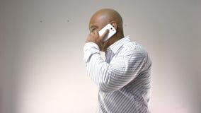 Homem de negócios africano que fala em casa no móbil vídeos de arquivo