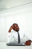 Homem de negócios africano que senta-se em seu local de trabalho Imagens de Stock