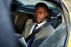 Homem de negócios africano Reading Newspaper no carro imagens de stock