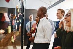 Homem de negócios africano de riso e sua sessão de reflexão da equipe com WTI fotos de stock