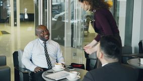 Homem de negócios afro-americano alegre na roupa formal que sorri e que discute o relatório financeiro com seu Caucasian filme